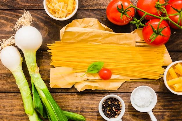 Especias y verduras alrededor de espagueti