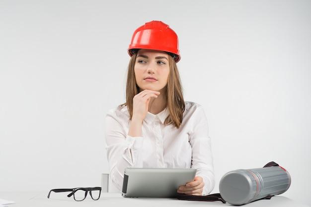 El espécimen de la mujer se sienta en la mesa en el casco naranja sostiene ipad