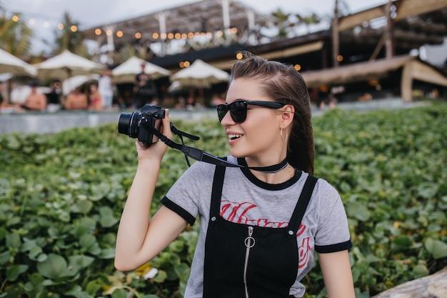 Espectacular chica con cabello castaño con cámara cerca de césped verde. foto exterior de atractiva mujer europea haciendo fotos en el parque.