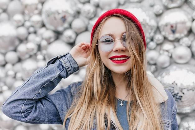 Espectacular chica en chaqueta vaquera a través de gafas azules. foto de dama alegre con peinado recto sonriendo en la pared brillante.