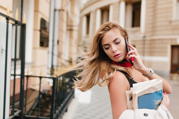 Espectacular chica ocupada con cabello rubio saludando apresurándose a la oficina y hablando por teléfono