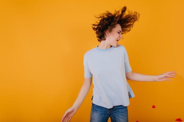 Espectacular chica de pelo corto en camiseta celeste bailando de placer