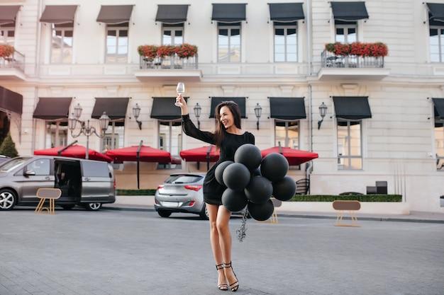 Espectacular dama de cabello negro levantando una copa de vino, mientras posa en la calle temprano en la noche