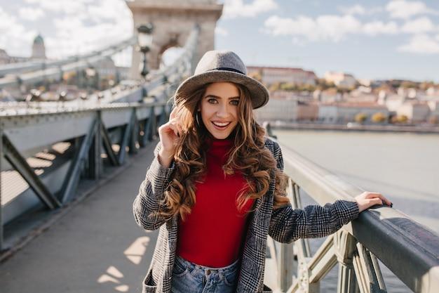 Espectacular modelo femenino blanco con sombrero posando sobre fondo de río y sonriendo