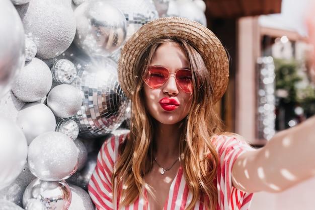 Espectacular modelo de mujer de buen humor haciendo selfie con expresión de cara de besos. foto al aire libre de elegante mujer rubia lleva sombrero de verano de pie cerca de bolas brillantes.