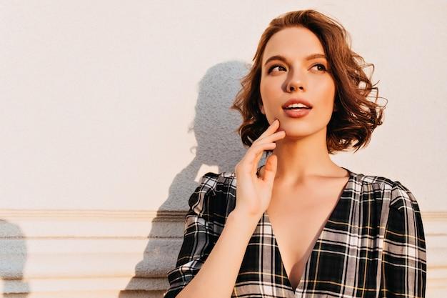 Espectacular mujer caucásica posando en un día soleado con expresión de cara de ensueño. foto al aire libre de linda chica elegante con peinado corto.