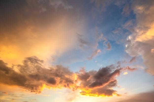 Espectacular paisaje del cielo al atardecer con nubes hinchadas iluminadas por el sol poniente naranja y cielos azules.
