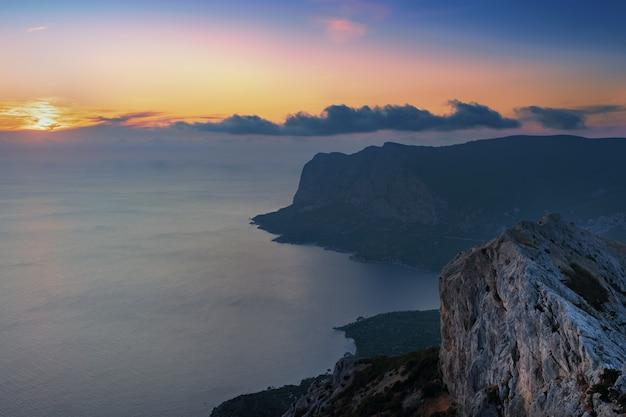 Espectacular puesta de sol sobre las montañas y el mar.