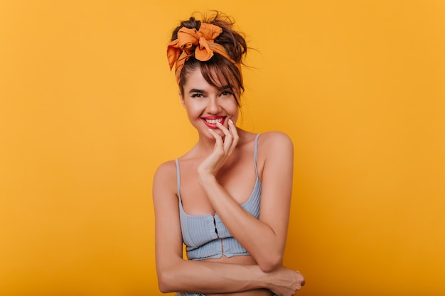 Espectacular señorita con cinta naranja en el cabello divirtiéndose