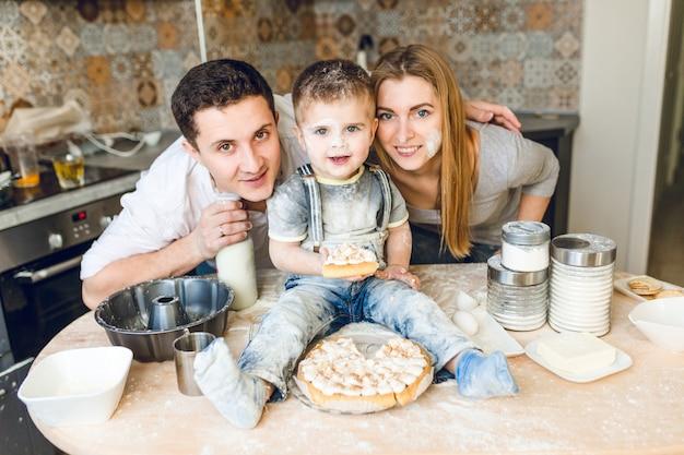 Espectáculo familiar de dos padres y un niño sentado en la mesa de la cocina jugando con harina y probando un pastel.