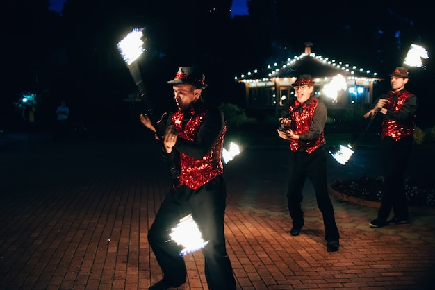 Espectáculo de fuego. los bailarines masculinos hacen girar antorchas de fuego