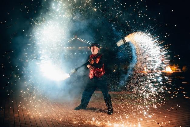 Espectáculo de fuego. un hombre gira un fuego antorchas brillantes