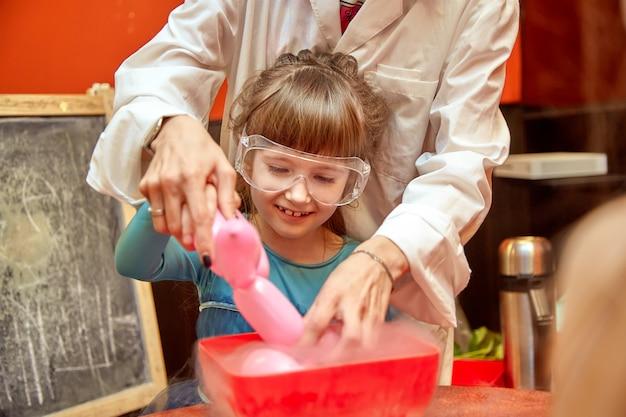 Espectáculo químico para niños. el profesor llevó a cabo experimentos químicos con nitrógeno líquido en la niña de cumpleaños.