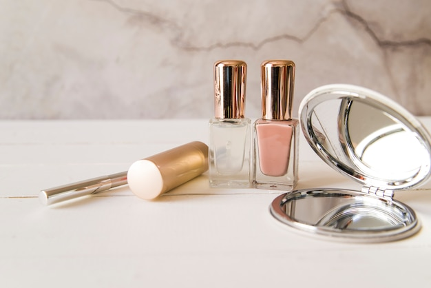 Espejo de bolsillo; lápiz labial; delineador de ojos y esmalte de uñas en la mesa