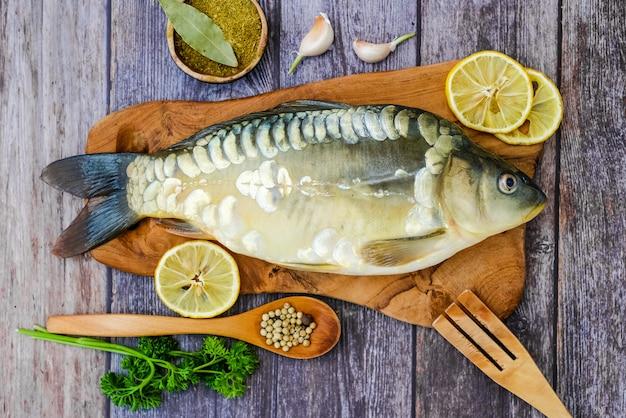 Espejo carpa en una tabla de cortar rodeada de verduras. pescado fresco antes de cocinar. pescado y verduras.