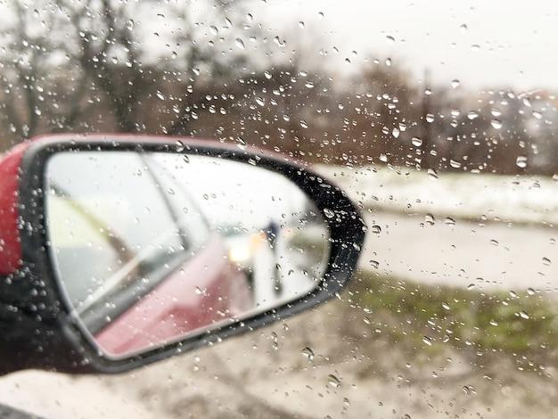 Espejo con un coche a través de la ventana con gotas de lluvia