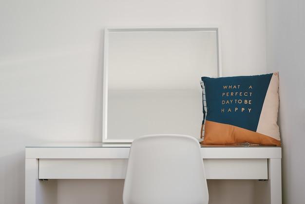 Espejo y cojín sobre una mesa blanca con una silla en frente