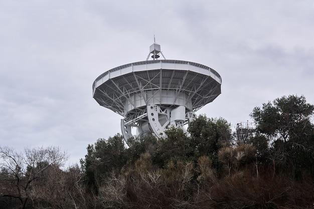 El espejo de un gran radiotelescopio astronómico, dirigido a un cielo nublado, es visible desde los árboles.