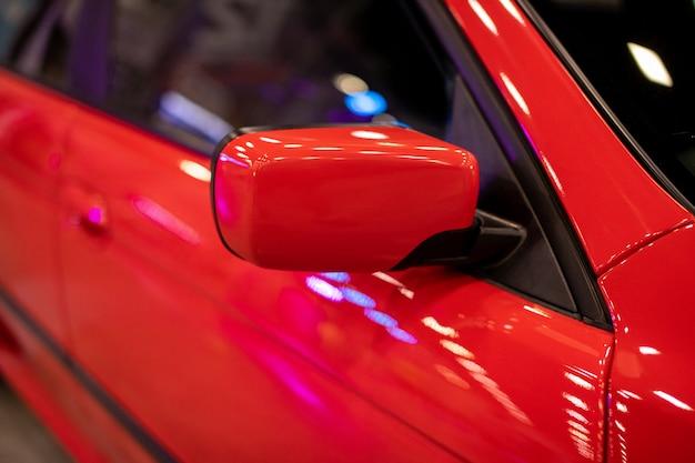 El espejo lateral de un auto deportivo rojo. espejo retrovisor.