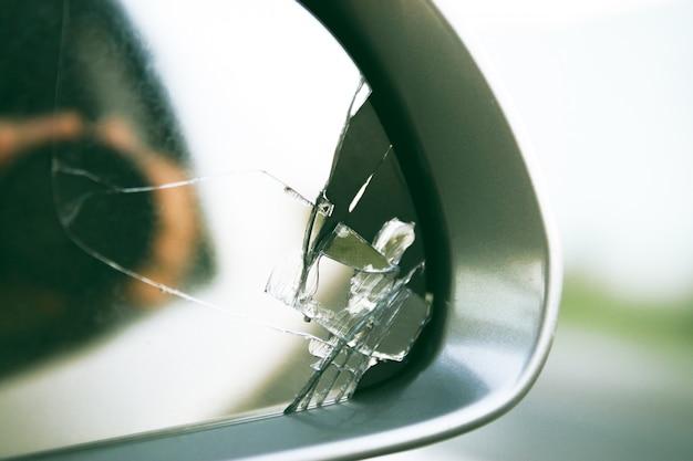 Espejo lateral del automóvil con vista hacia atrás. espejo roto de cerca.