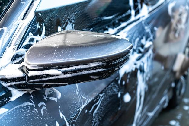 Espejo lateral de coche de primer plano con espuma de lavado de coches