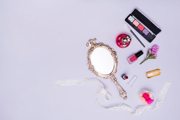 Espejo de mano de la vendimia; lápiz labial; esmalte de uñas; esponja; botella de perfume y paleta de sombra de ojos sobre fondo morado