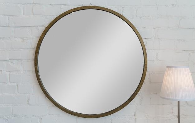 Espejo de marco dorado vintage de forma redonda en pared de ladrillo blanco