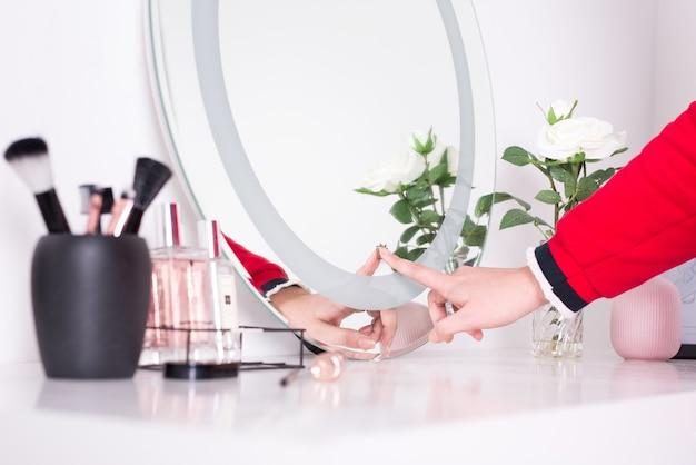 Espejo redondo con algunas herramientas de maquillaje y una rama de rosa blanca junto a él.