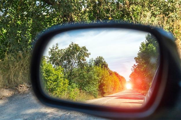 Espejo retrovisor de conducción de automóviles vista bosque verde y camino de pueblo