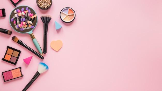 Espejo con sombras de ojos y pinceles en polvo sobre mesa rosa.