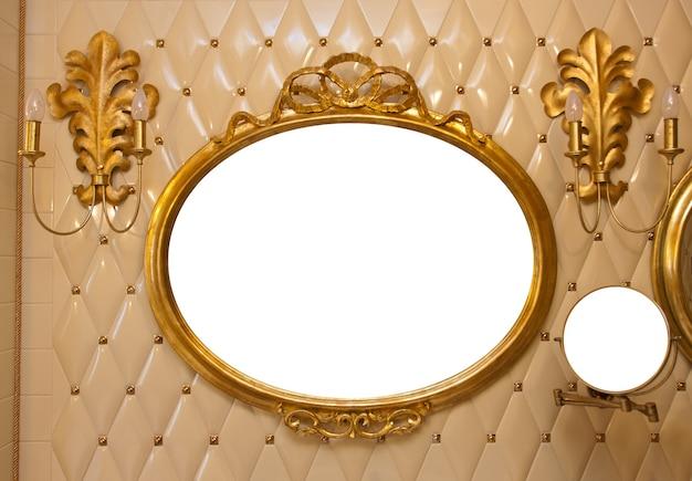 Espejo vintage de lujo con marco dorado en la pared. aislado por dentro