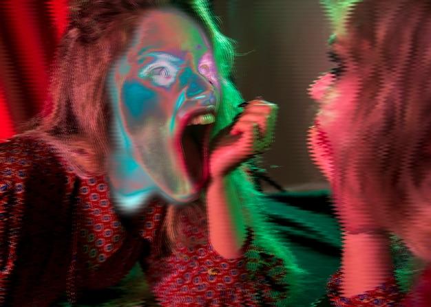 Espeluznante cara glitched de una mujer mirándose en el espejo