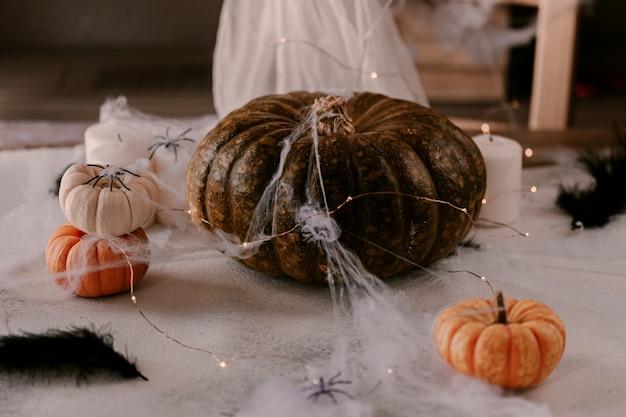 Espeluznante decoración de halloween con diferentes calabazas, luz, arañas.
