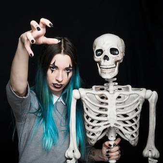 Espeluznante mujer joven con espeluznante esqueleto