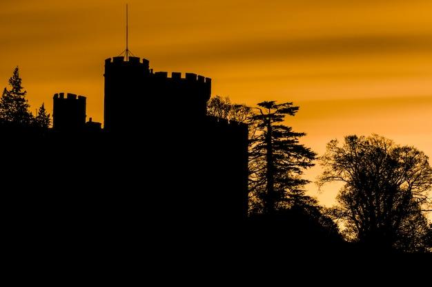 Espeluznante silueta de un castillo y árboles con cielo naranja