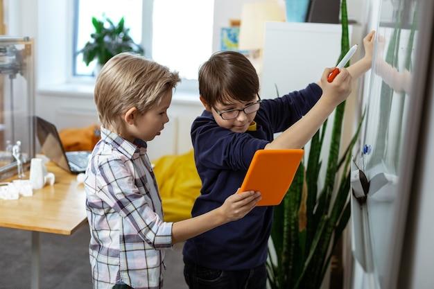 Esperando al maestro. chico rubio con tableta naranja mientras su amigo escribe en el escritorio y mira en la pantalla