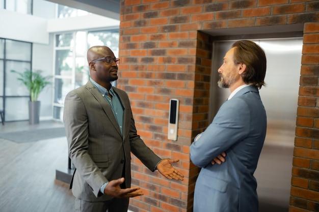 Esperando ascensor. dos hombres de negocios hablando mientras esperan el ascensor en el centro de negocios