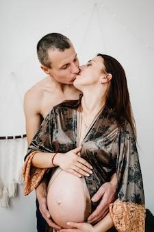Esperando bebé. mujer sexy embarazada de pie en la habitación y las manos del hombre abraza un vientre redondo