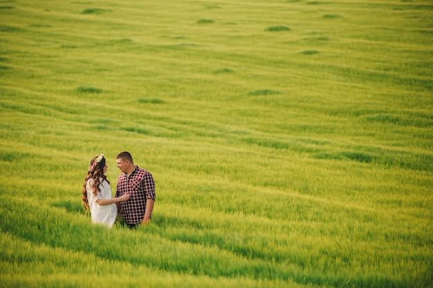 Esperando bebe. paternidad. la mujer joven embarazada y su marido están felices de tomarse de las manos, yendo al aire libre en el campo de fondo de hierba verde. enfoque selectivo