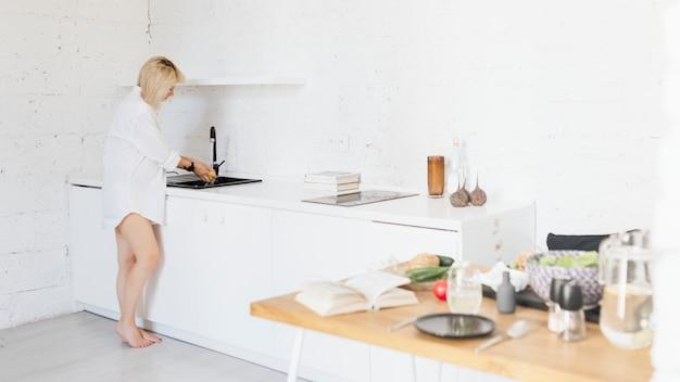 Esperando madre lavando platos en la cocina.
