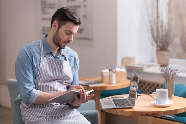 Esperando una musa. grave joven guapo tomando notas y usando la computadora portátil mientras está sentado en un sillón.