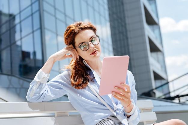 Esperando novio. mujer joven con gafas leyendo un libro interesante mientras espera a su novio
