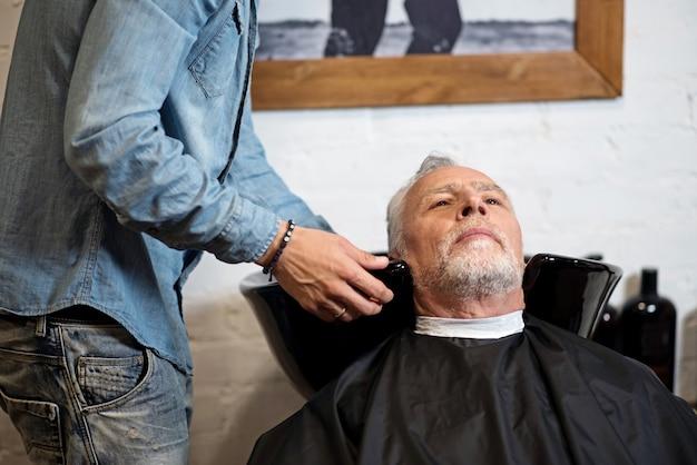 Esperando un refrigerio. anciano pensativo sentado en la peluquería mientras su cabello es lavado por un especialista.