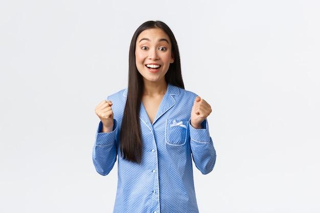 Esperanza emocionada chica asiática en pijama azul aprieta los puños y mira la cámara de regocijo, sonriendo mientras espera una gran noticia, sintiéndose entusiasta y optimista mientras está parado sobre fondo blanco