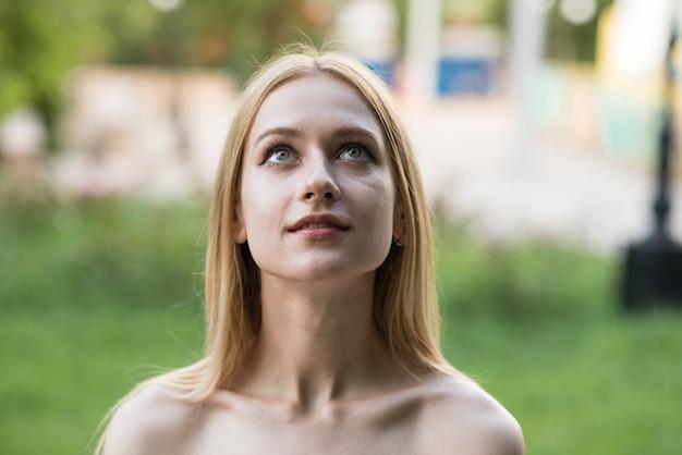 Esperanza mujer caucásica de pie afuera mirando al cielo en contemplación