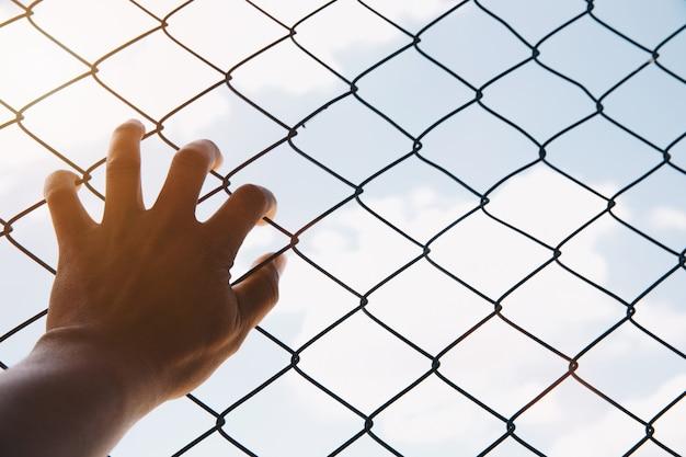 Espere el concepto, la mano infeliz del hombre triste desesperada en la prisión de la cerca en la cárcel, no libre y el concepto adolescente de la lucha.