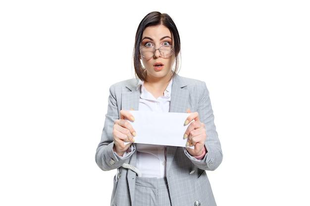 Espero que sea solo un pago por adelantado. mujer joven en traje gris ganando un pequeño salario y sin creer lo que ve. conmocionado e indignado. concepto de problemas, negocios, problemas y estrés del oficinista.