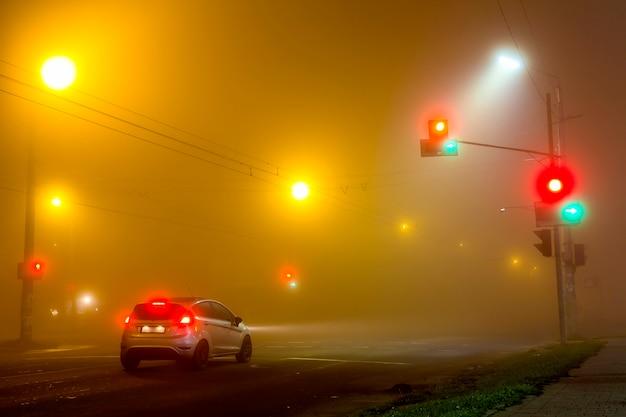 Espesa niebla sobre carretera vacía con coche solitario y semáforos en la noche