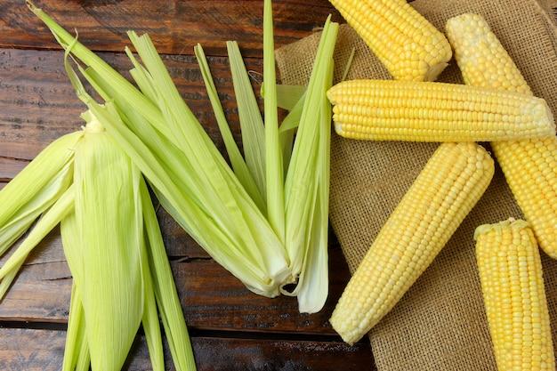 Espiga de maíz crudo, cosechada de la plantación, sobre tela rústica, sobre mesa de madera rústica.