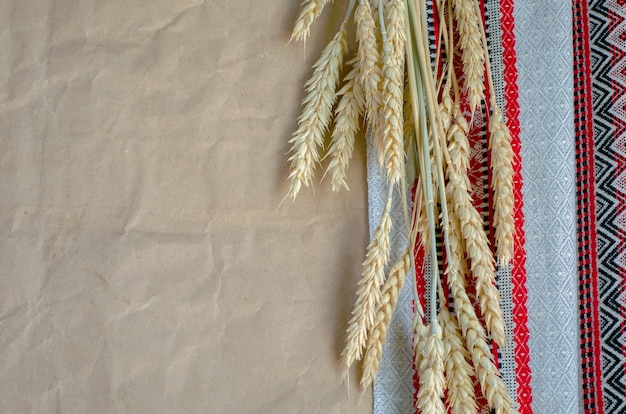 Espiguillas de centeno maduras de tela bordada popular y papel marrón de paquete de envoltura